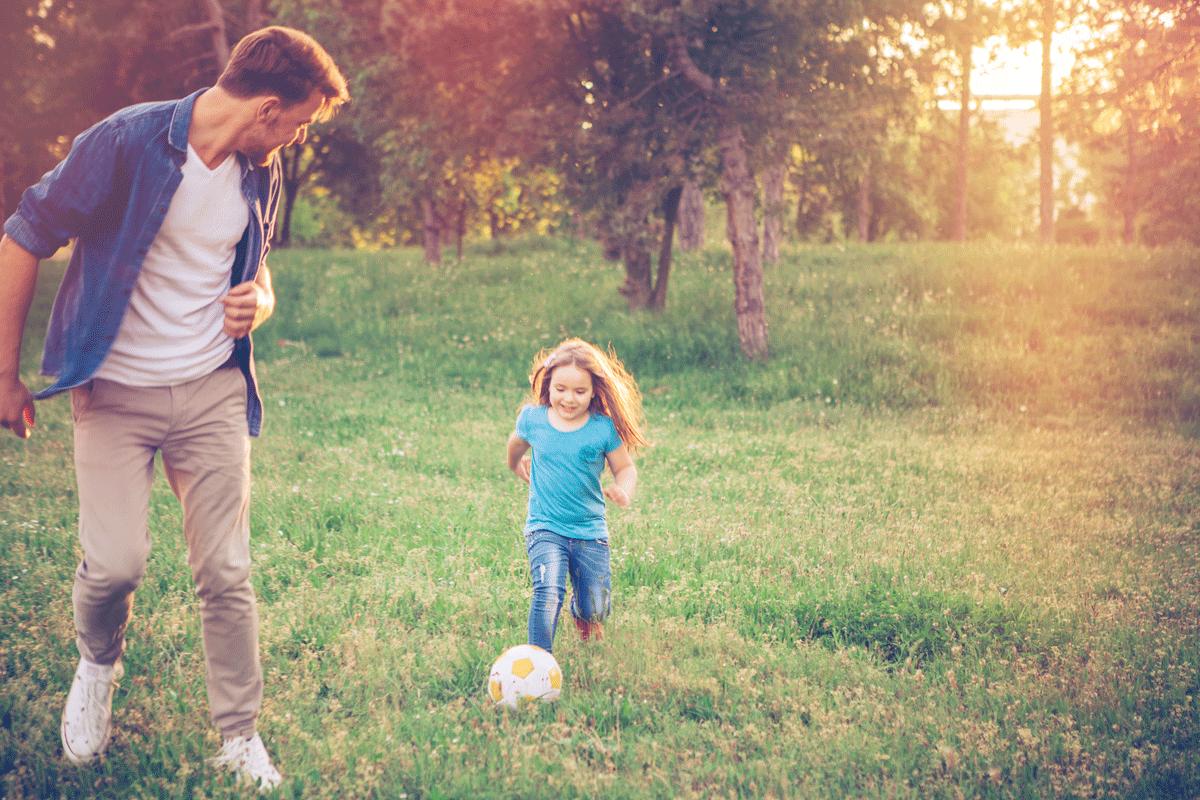 Un père et sa fille jouant au soccer